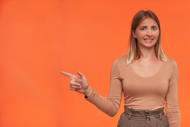 Zdezorientowana młoda, ładna białogłowa kobieta z krótką fryzurą, krzywiąca się zmieszana, wskazująca na bok palcem wskazującym, odizolowana na pomarańczowej ścianie