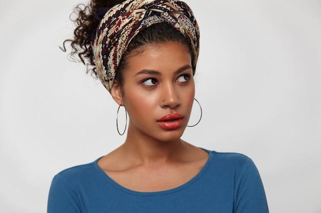 Zdezorientowana młoda, ładna ciemnowłosa, kręcona dama z przypadkową fryzurą, wyglądająca dziwnie na bok, stojąc na białym tle w kolorowych ubraniach