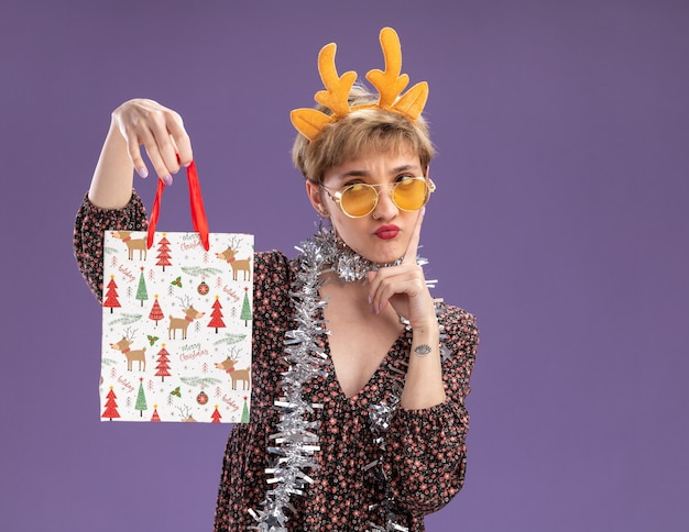 Zdezorientowana młoda ładna dziewczyna nosząca opaskę z poroża renifera i blichtrową girlandę wokół szyi w okularach trzymająca torbę prezentów świątecznych, patrząc na nią, dotykająca twarzy odizolowanej na fioletowej ścianie z kopią miejsca