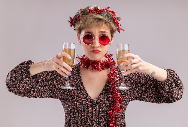 Zdezorientowana młoda ładna dziewczyna ubrana w świąteczny wieniec na głowę i świecącą girlandę wokół szyi w okularach, trzymając dwie szklanki szampana, patrząc na kamery na białym tle