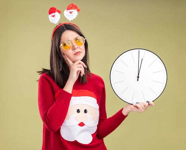 Zdezorientowana młoda ładna kaukaska dziewczyna ubrana w sweter świętego mikołaja i opaskę na głowę w okularach trzymających zegar trzymając rękę na podbródku patrząc na bok na białym tle na oliwkowo-zielonym tle