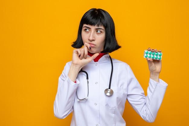Zdezorientowana młoda ładna kaukaska kobieta w mundurze lekarza ze stetoskopem trzymająca opakowanie pigułki i kładąca rękę na brodzie, patrząc na bok