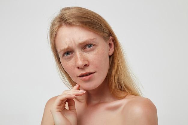 Zdezorientowana młoda, ładna ruda kobieta z długimi włosami marszczy brwi, trzymając podniesioną dłoń na brodzie, stojąc nad białą ścianą