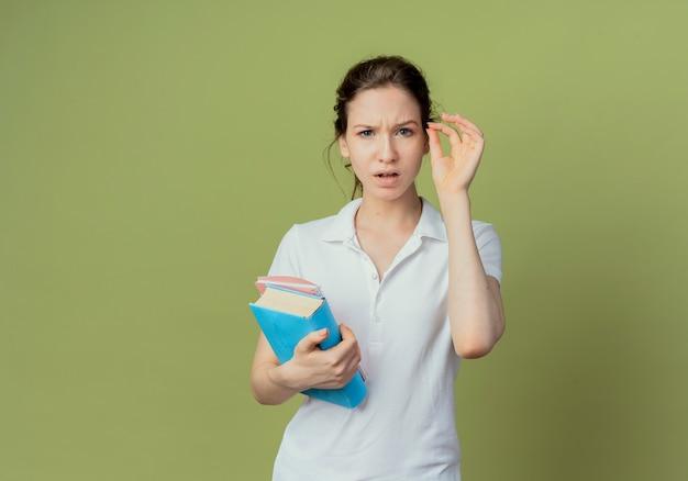Zdezorientowana młoda ładna studentka trzymająca książkę i notatnik trzymająca rękę w powietrzu udawać, że trzyma coś izolowanego na oliwkowozielonym tle z miejscem na kopię