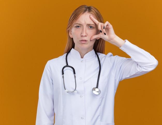 Zdezorientowana młoda lekarka imbirowa ubrana w szatę medyczną i stetoskop dotykająca twarzy