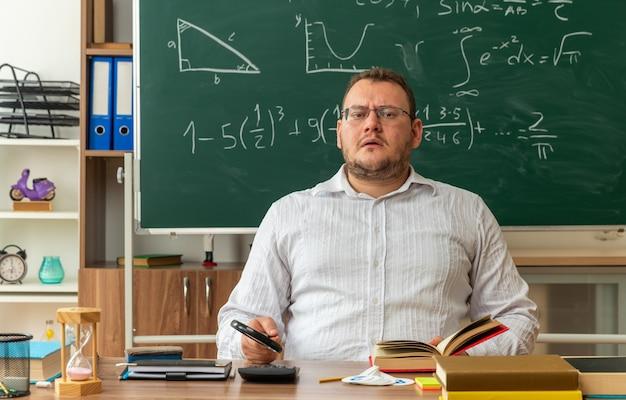 Zdezorientowana młoda nauczycielka blondynka w okularach, siedząca przy biurku z szkolnymi narzędziami w klasie, trzymająca szkło powiększające, chwytając otwartą książkę patrząc na kamery