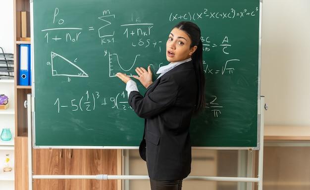 Zdezorientowana młoda nauczycielka stojąca przed tablicą przy tablicy w klasie