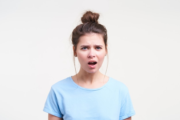 Zdezorientowana młoda niebieskooka ładna brunetka kobieta z przypadkową fryzurą wykrzywiającą twarz, patrząc zdezorientowana z przodu, odizolowana na białej ścianie