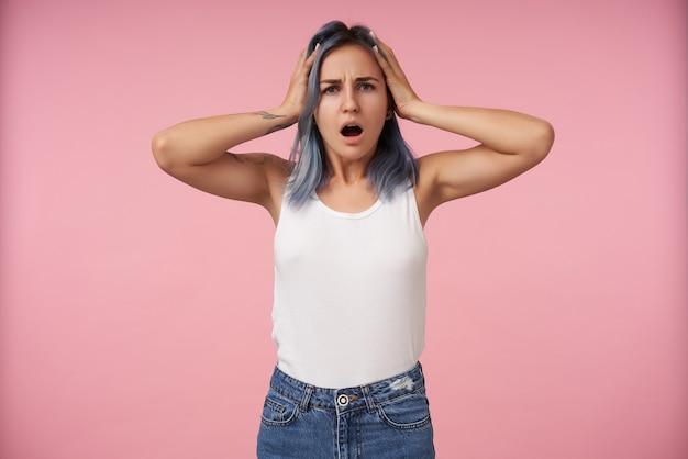 Zdezorientowana młoda niebieskowłosa kobieta z tatuażami, ściskająca głowę z podniesionymi rękami i wyglądająca zdumiewająco, odizolowana na różowo