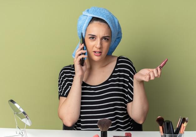 Zdezorientowana młoda piękna dziewczyna siedzi przy stole z narzędziami do makijażu owiniętymi włosami w ręcznik, mówi na telefonie trzymając szminkę na białym tle na oliwkowozielonej ścianie