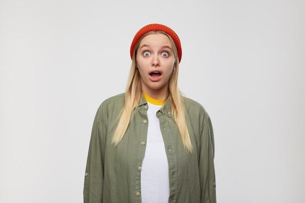 Zdezorientowana młoda siwowłosa kobieta z niezobowiązującą fryzurą wyglądająca zdumiewająco z szeroko otwartymi oczami i ustami, odizolowana na niebiesko