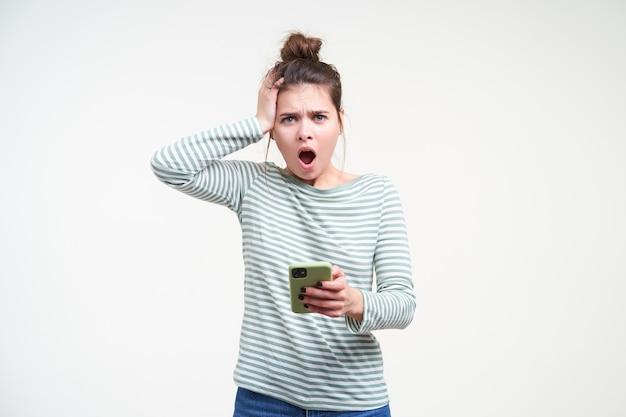 Zdezorientowana młoda śliczna brązowowłosa kobieta z przypadkową fryzurą trzymająca podniesioną dłoń na głowie, patrząc emocjonalnie z przodu z otwartymi ustami, odizolowana na białej ścianie