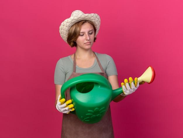 Zdezorientowana młoda słowiańska ogrodniczka w kapeluszu ogrodniczym i rękawiczkach, trzymająca i patrząca na konewkę