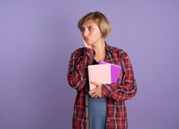 Zdezorientowana młoda słowiańska studentka kładzie rękę na twarzy trzyma książkę i notatnik patrząc na bok looking