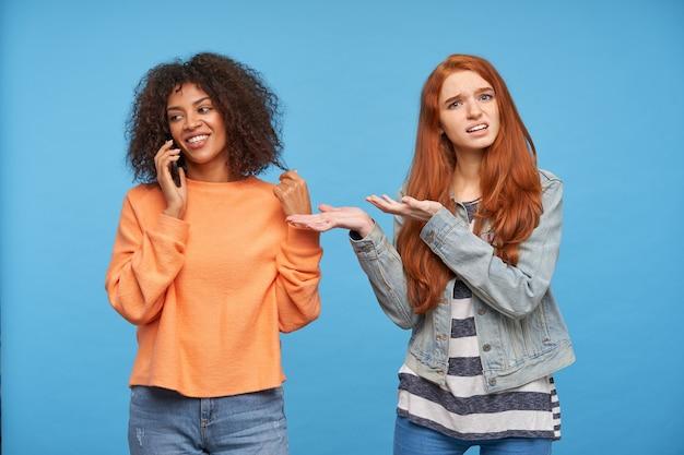 Zdezorientowana młoda, urocza ruda kobieta pokazuje zmieszaną z uniesionymi rękami swoją pozytywną brązowowłosą ciemnoskórą brunetkę z telefonem komórkowym, odizolowaną na niebieskiej ścianie
