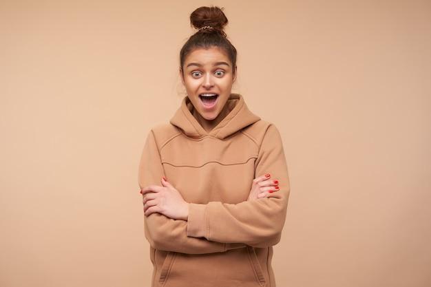 Zdezorientowana młoda zielonooka brunetka ubrana w nagą bluzę patrzy z podekscytowaniem przed siebie z szeroko otwartymi ustami i złożonymi rękami na piersi, pozując nad beżową ścianą