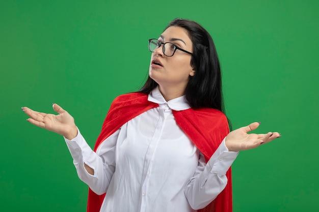 Zdezorientowana nieporozumienie młoda superkobieta w okularach trzyma puste ręce w górze i nie rozumie, co się dzieje, patrząc prosto odizolowana na zieloną ścianę