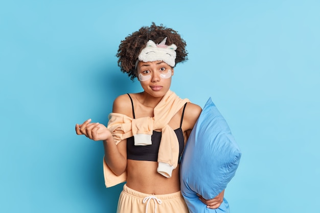 Zdezorientowana, niezdecydowana młoda kobieta w piżamie wzrusza ramionami i czuje się niepewna, że coś trzyma poduszkę nie zna planów na dzień stoi w domu pod niebieską ścianą