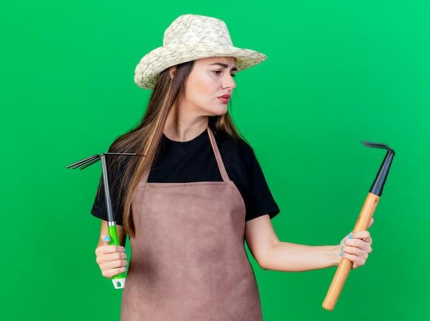Zdezorientowana piękna ogrodniczka w mundurze w kapeluszu ogrodniczym, trzymając grabie motyka i patrząc na grabie w dłoni na białym tle na zielonym tle