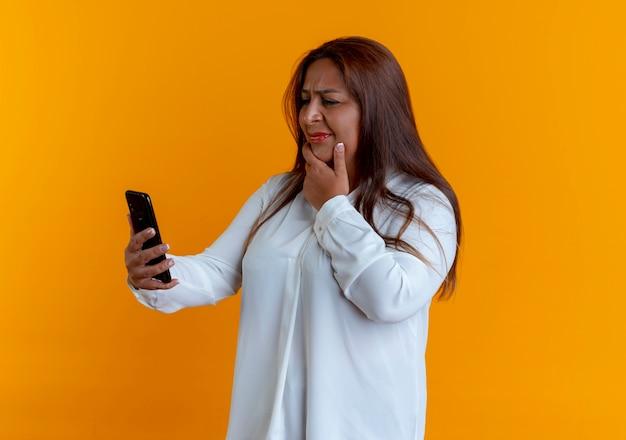 Zdezorientowana przypadkowa kaukaski kobieta w średnim wieku, trzymając i patrząc na telefon i kładąc rękę na brodzie