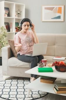 Zdezorientowana rozkładająca dłoń młoda dziewczyna z laptopem w słuchawkach siedząca na kanapie za stolikiem kawowym w salonie