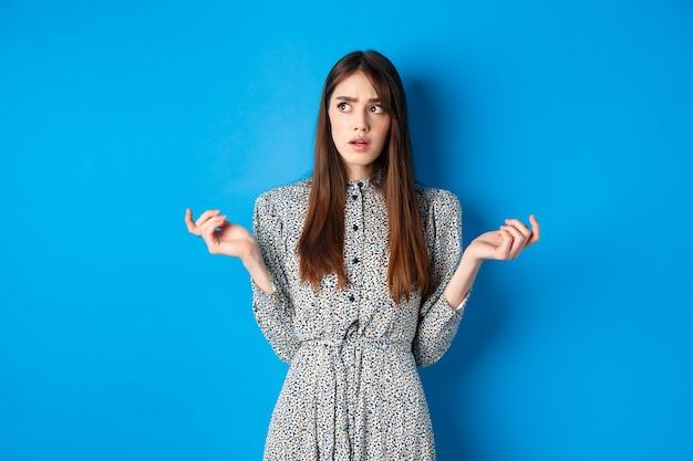 Zdezorientowana śliczna dziewczyna nie może czegoś zrozumieć, odwraca wzrok w zamyśleniu i liczy na palcach, stoi w sukience na niebiesko.