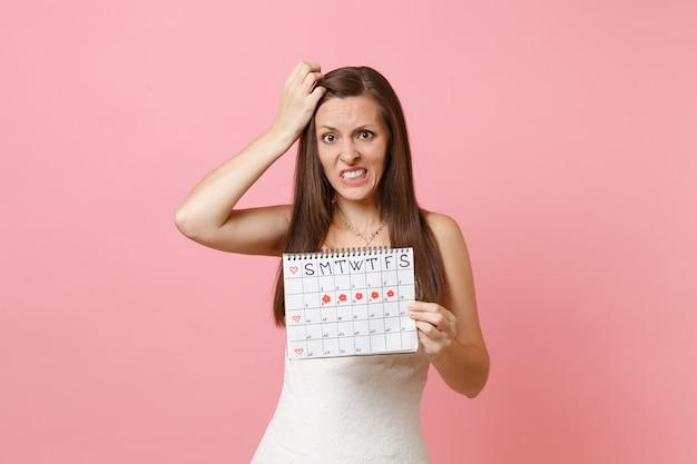Zdezorientowana winna kobieta w białej sukni trzyma się w głowie, patrząc na kalendarz kobiecych miesiączek, aby sprawdzić dni menstruacyjne