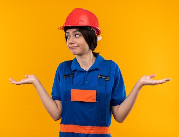 Zdezorientowana, wyglądająca na rozłożone ręce, młoda kobieta budowlana w mundurze