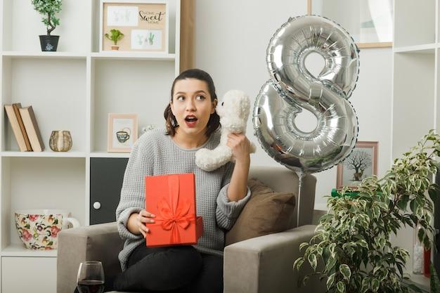 Zdezorientowana wyglądająca strona piękna dziewczyna na szczęśliwy dzień kobiet trzymająca prezent z misiem siedzącym na fotelu w salonie