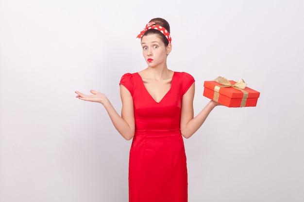 Zdezorientowana, zaintrygowana urocza kobieta trzymająca pudełko, powiedzmy nie wiem. wewnątrz, studio strzał, na białym tle na szarym tle