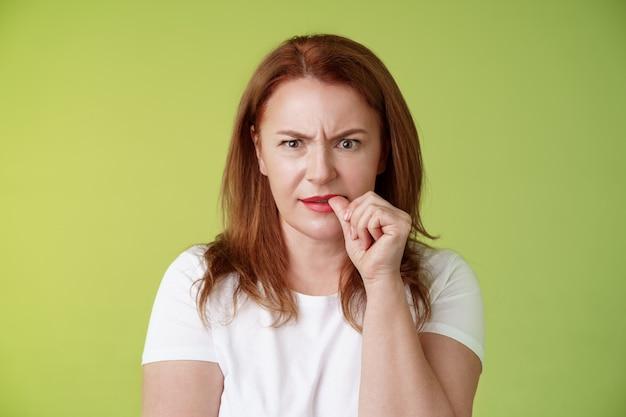 Zdezorientowana zdziwiona ruda matka w średnim wieku zdezorientowana spojrzenie zmartwiona rozwiązywanie kłopotliwej sytuacji rozważanie rozwiązania gryzienie paznokcia kciuka marszczy brwi intensywne spojrzenie kamera myślenie w zamyśleniu