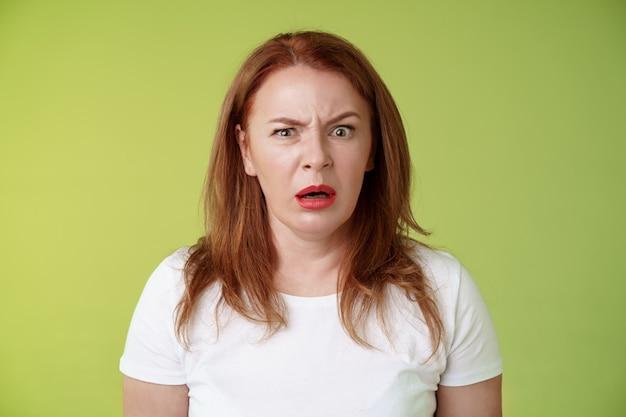Zdezorientowana, zszokowana, sapiąca, ruda kobieta w średnim wieku wzdrygnęła się sfrustrowana zaintrygowana otwarte usta oniemiały dziwak dziwna szokująca scena stać zielona ściana zdumiona rozczarowana