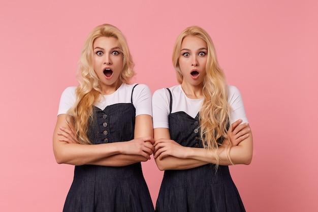 Zdezorientowane młode, dość długowłose blondynki kobiety ubrane w eleganckie ubrania, trzymając złożone ręce, patrząc zdumiewająco na aparat z szeroko otwartymi oczami, pozując na różowym tle