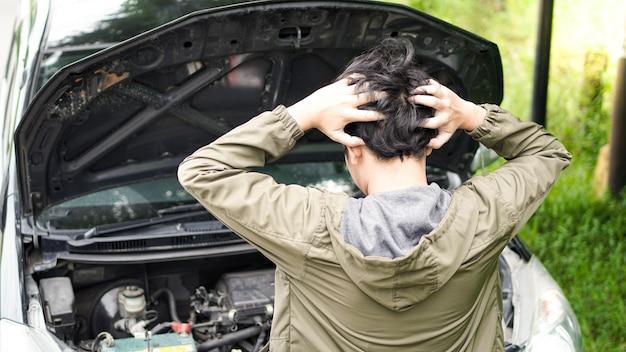Zdezorientowany azjata otworzył maskę samochodu