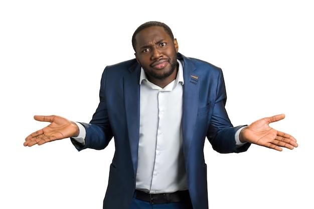 """Zdezorientowany biznesmen na białym tle. nie jestem pewien, czy amerykański menedżer robi gest """"nie wiem""""."""