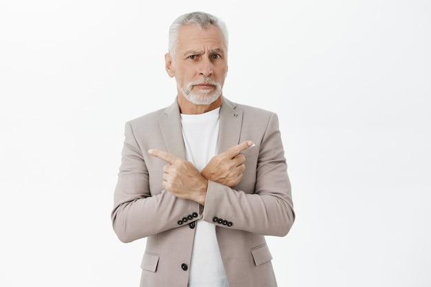 Zdezorientowany brodaty biznesmen w garniturze, wskazując palcami na boki, dokonując wyboru, nie może się zdecydować