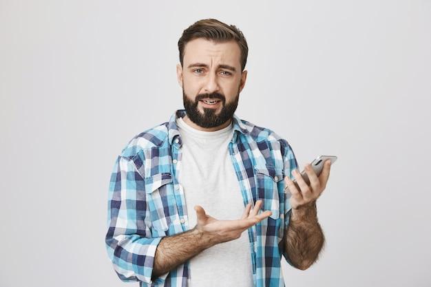 Zdezorientowany brodaty facet wzrusza ramionami, nie rozumiem, jak korzystać z aplikacji na telefon komórkowy