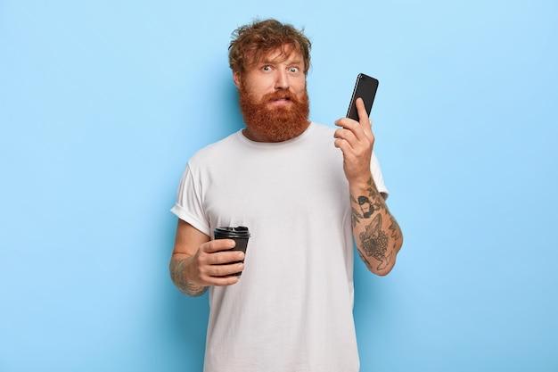 Zdezorientowany brodaty rudowłosy facet trzyma telefon komórkowy, odbiera telefon od nieznanej osoby, słyszy okropny głośny krzyk przez komórkę, pije kawę na wynos, nosi białą swobodną koszulkę