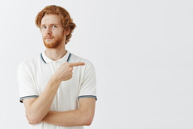 Zdezorientowany brodaty rudy facet pozuje przy białej ścianie