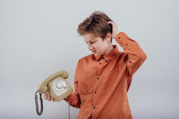 Zdezorientowany chłopiec ze starym telefonem na białym tle