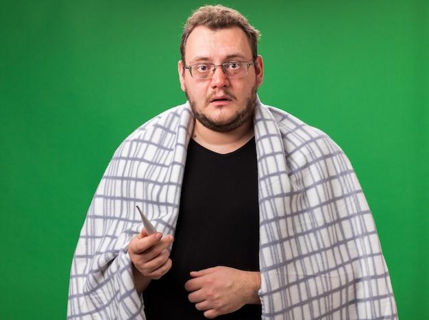 Zdezorientowany chory mężczyzna w średnim wieku owinięty w kratę trzymającą termometr odizolowany na zielonej ścianie