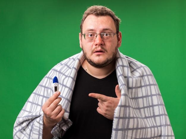 Zdezorientowany, chory mężczyzna w średnim wieku, owinięty w szkocką kratę i wskazujący na termometr odizolowany na zielonej ścianie