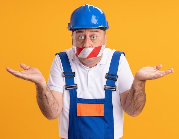 Zdezorientowany dorosły budowniczy mężczyzna w mundurze zakrywa usta taśmą klejącą i trzyma ręce otwarte na białym tle na pomarańczowej ścianie