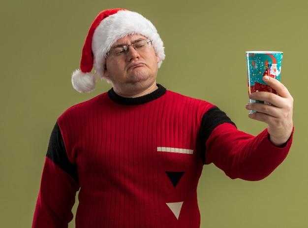 Zdezorientowany dorosły mężczyzna w okularach i czapce świętego mikołaja, trzymający świąteczną filiżankę kawy, rozciągając ją i patrząc na nią na białym tle na oliwkowozielonej ścianie