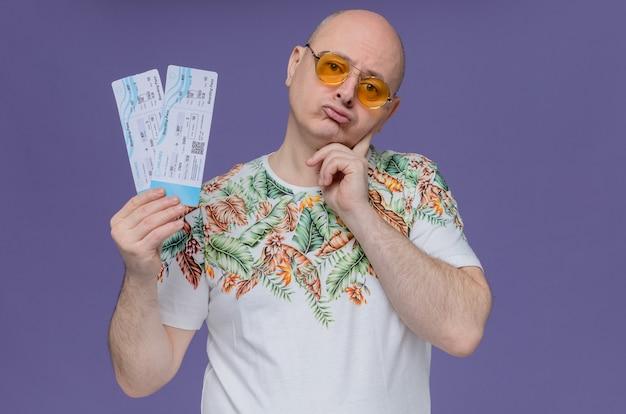 Zdezorientowany dorosły mężczyzna w okularach przeciwsłonecznych trzymający bilety lotnicze