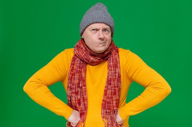 Zdezorientowany dorosły słowiański mężczyzna w czapce zimowej i szaliku na szyi, kładąc ręce na jego talii i patrząc z boku