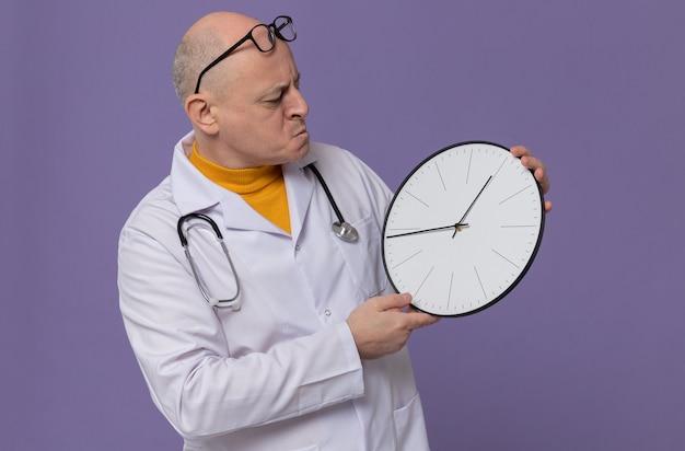 Zdezorientowany dorosły słowiański mężczyzna w okularach optycznych w mundurze lekarza, trzymający stetoskop i patrzący na zegar