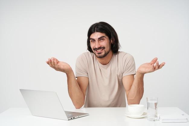 Zdezorientowany facet, niezadowolony biznesmen z czarnymi włosami i brodą. koncepcja biura. siedząc w miejscu pracy. wzrusza ramionami. oglądanie z uśmiechem, odizolowane na białej ścianie