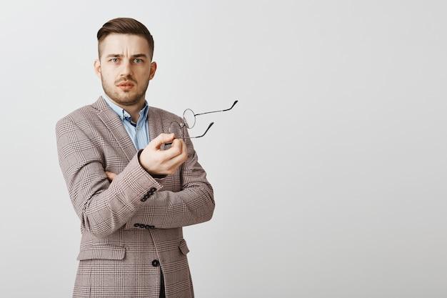 Zdezorientowany i niezadowolony biznesmen zdejmuje okulary i wygląda na sfrustrowanego
