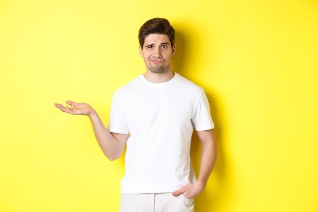 Zdezorientowany i niezadowolony facet podniósł rękę, krzywiąc się zdziwiony, stojąc na żółtym tle
